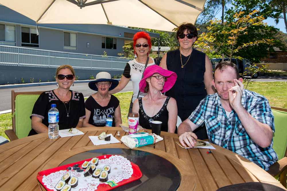 Clients, disability support workers and friends relax on the grounds of the new Kincumber residential site.